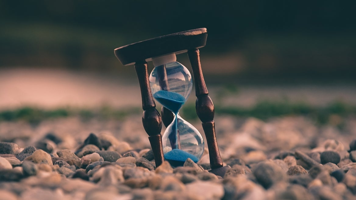 A photo of a hourglass on a pile of stones