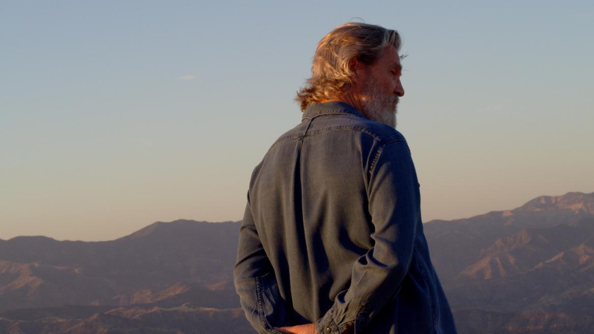 still of man with mountains behind him from documentary